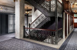 View of hotel hallway with staircase and elevator landing