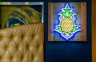 Pineapple logo sign on hotel lobby wall
