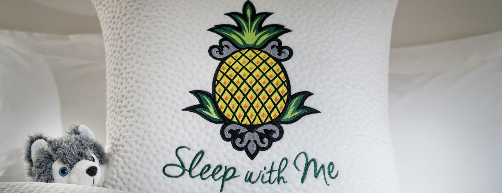 Detail of pillow on bed with sleep with me logo