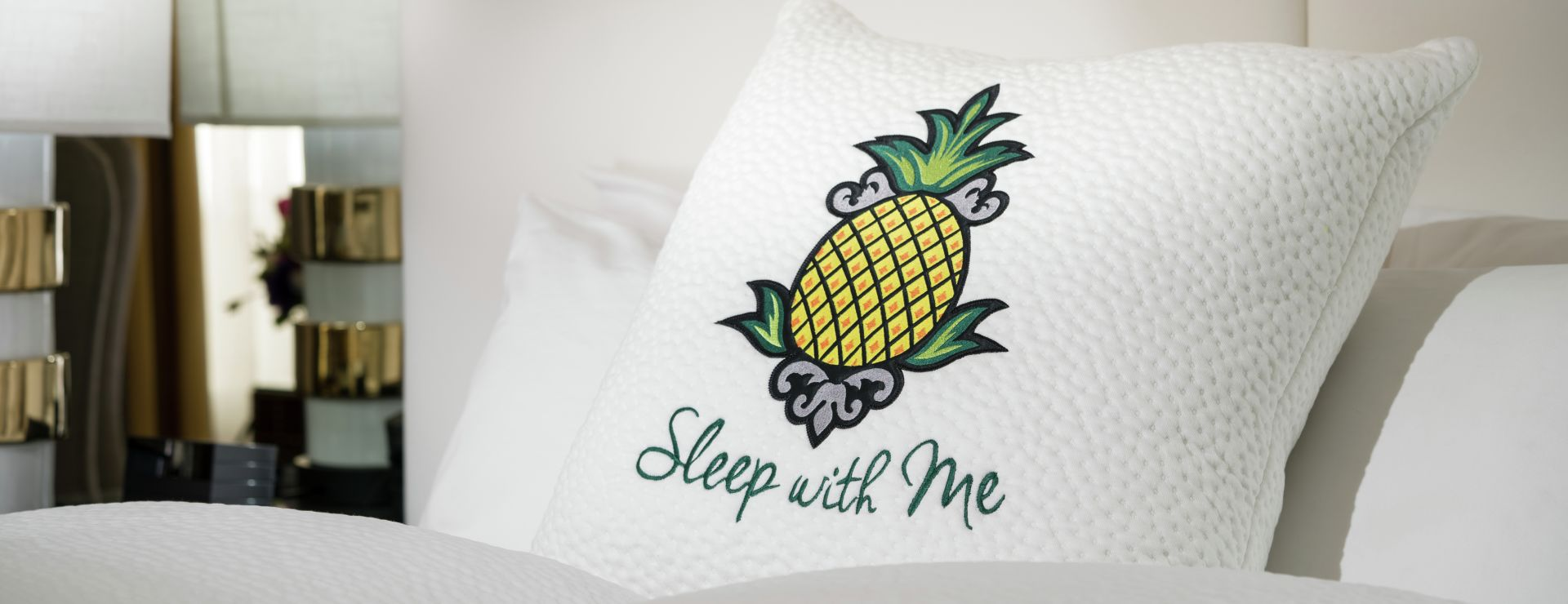 Sleep with me logoed pillow on guestroom bed