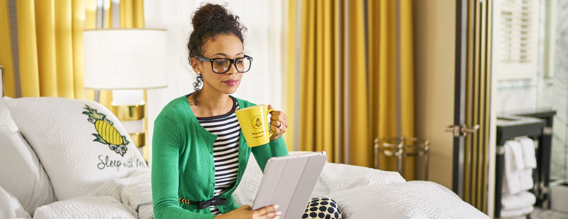 Women sitting on bed reading tablet and drinking from coffee mug