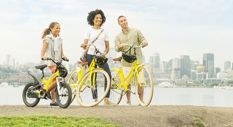 Family with hotel loaner bikes over looking the city skyline