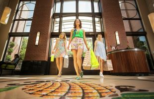 Three women with shopping bags walking through hotel lobby