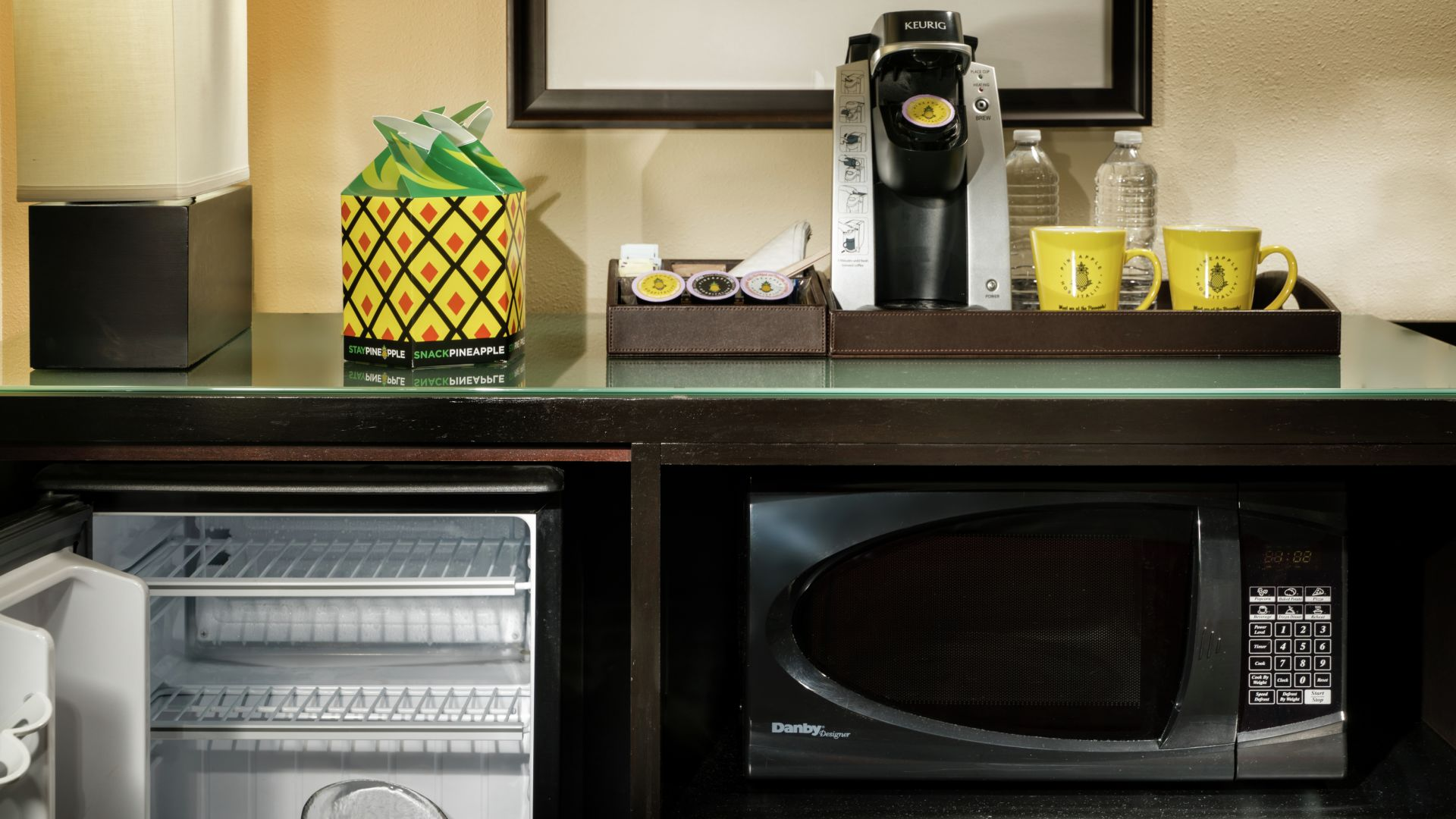 Coffee maker, microwave, and mini-fridge area in the Duet Queen Hill guestroom