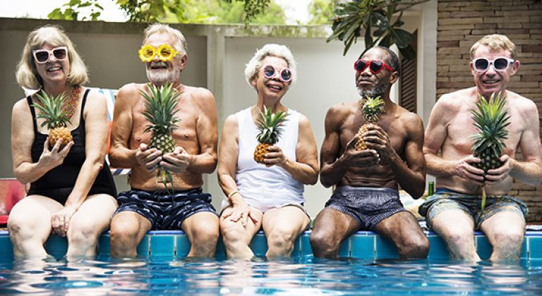 Group of people sitting on edge of swimming pool holding pineapples