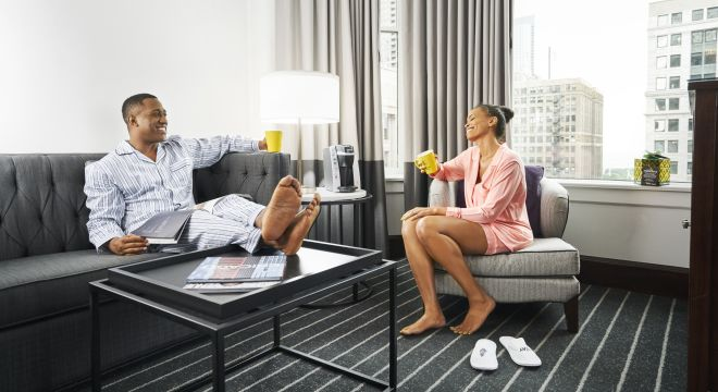 Couple drinking coffee in hotel guestroom