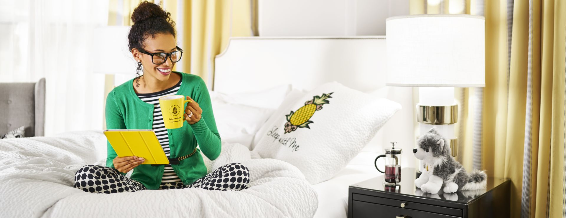 Women on guestroom bed on tablet and drinking coffee