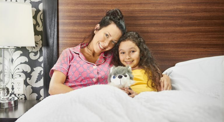 Mother and daughter in hotel bed with dash husky doll