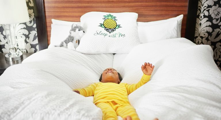 Young boy falling into hotel bed pillows and comforter