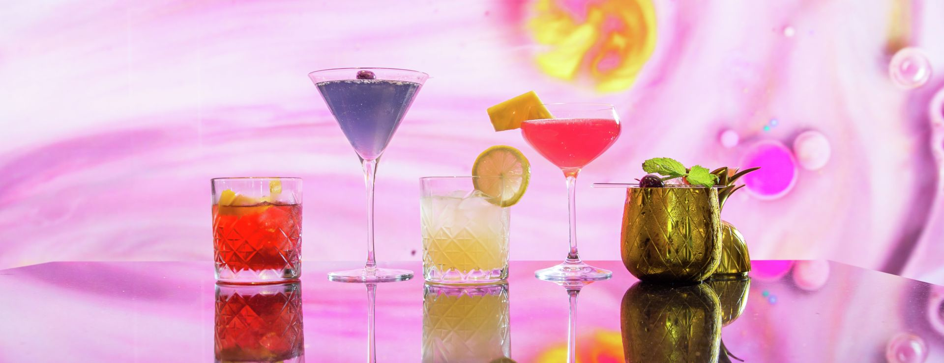 Variety of cocktails lined up on table with abstract background