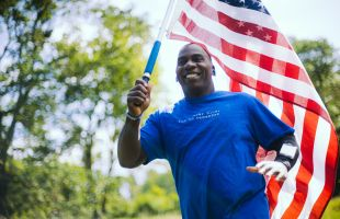 A man in blue shirt carrying an American flag