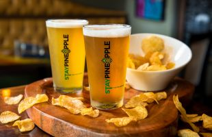 Pint glasses with draft beer and potato chips