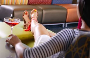 A woman enjoying a drink with her legs kicked up