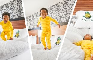 A Small Child jumping On A Bed